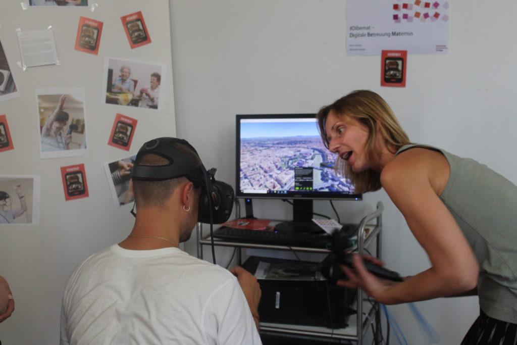 Eine Betreuerin probiert mit einem Teilnehmenden eine Virtual-Reality-Brille.