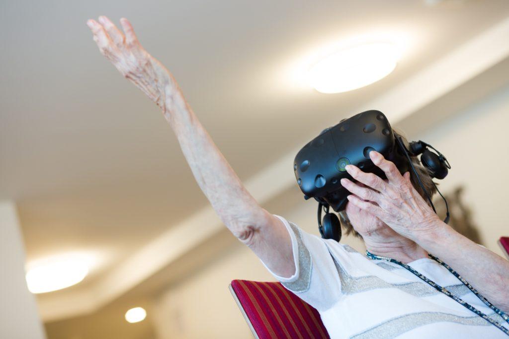 Alte Dame mit VR-Brille tastet
