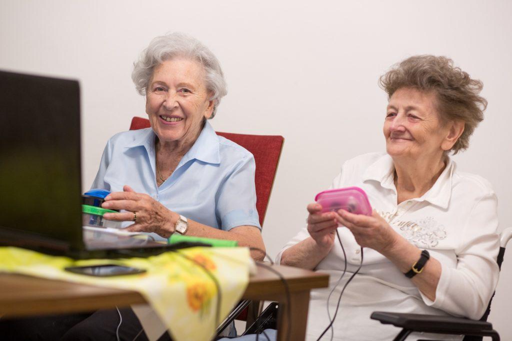 Zwei ältere Damen spielen zusammen digital